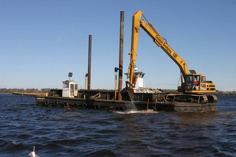 Concrete bridge rubble being downloaded to AR 398 in the New River